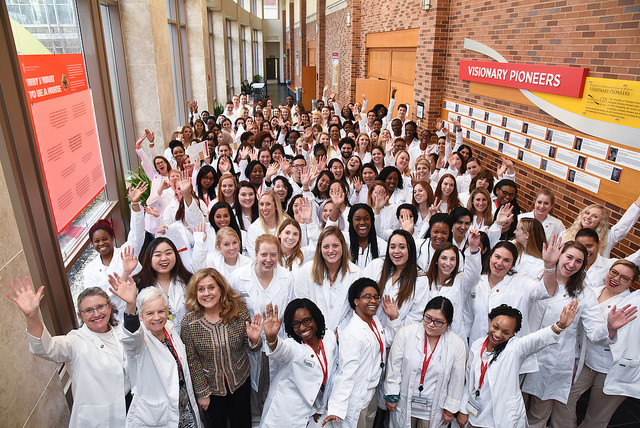 a group of students in white coats