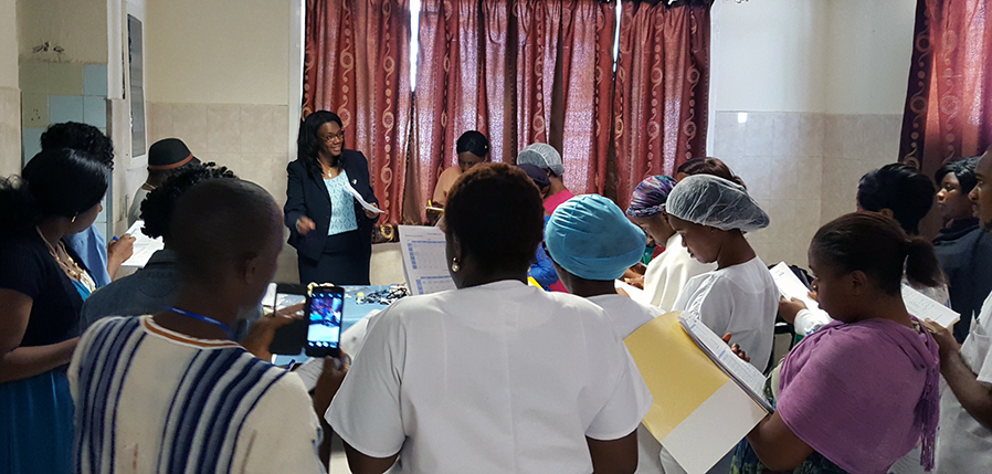 a representative from the Office of Global Health talks with health care workers