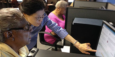 a nurse researcher helping a patient with a patient portal