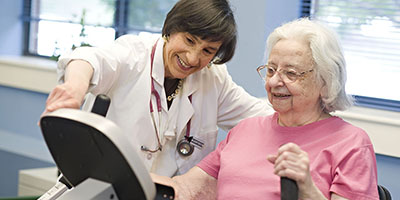 a nurse research with a patient on an exercise machine