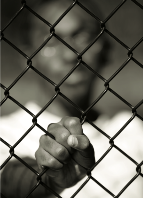 a man behind a chain-link fence
